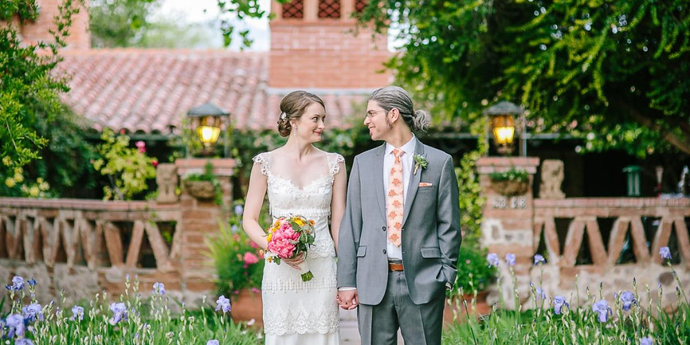 Bride in groom in front of adobe hacienda with lavender iris blooming.
