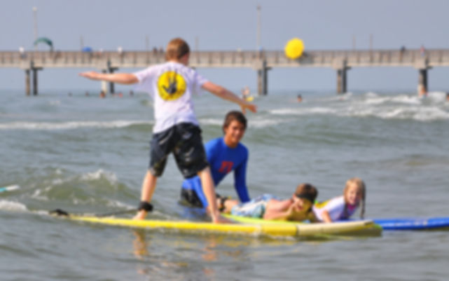 kids surfing with instructor Bob Hall Pier