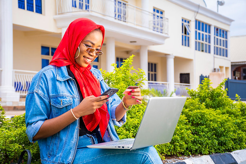 beautiful-young-african-woman-smiling-while-using-her-laptop-outside.jpg