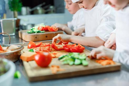 Children grind vegetables in the kitchen