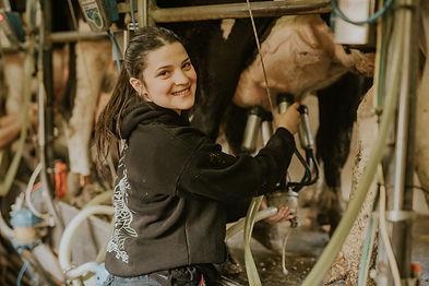 נערה מחייכת חולבת פרה בכפר הנוער בן שמן