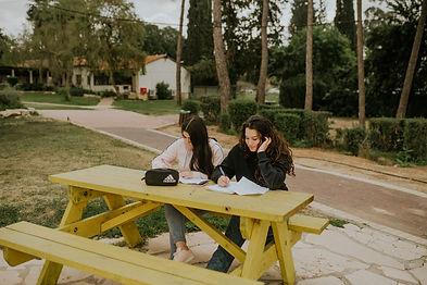 תמונה של שתי נערות יושבות על ספסל צהוב עושות שיעורי בית