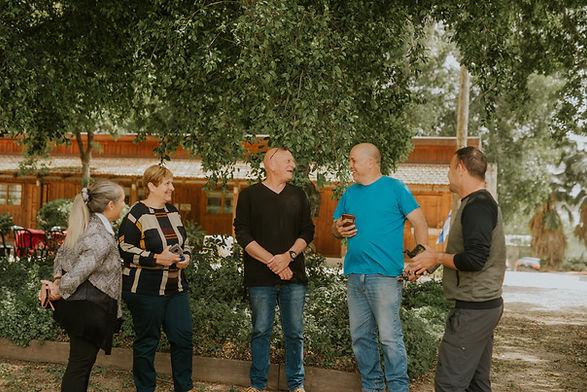 חמישה חברי צוות הכפר עומדים יחד ומדברים וצוחקים