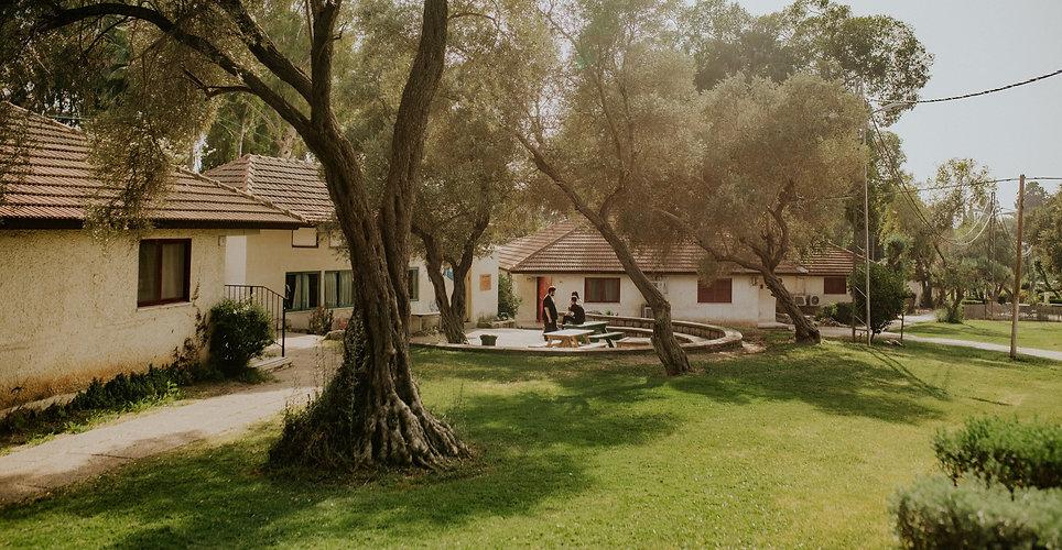 תמונת רקע של כפר הנוער בן שמן ובמרכזה 3 חניכים מדבירם