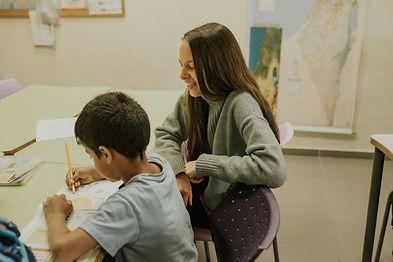 תמונה של מורה עוזרת לתלמיד בישעורי הבית שלו