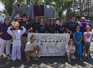 Summer workshop participants and staff pose with banner i front of a large elephat setpiece in the street before a parade.