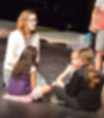 Teenage actress sitting in a circle on stage with 3 young actresses during a summer workshop team buildign excersise..