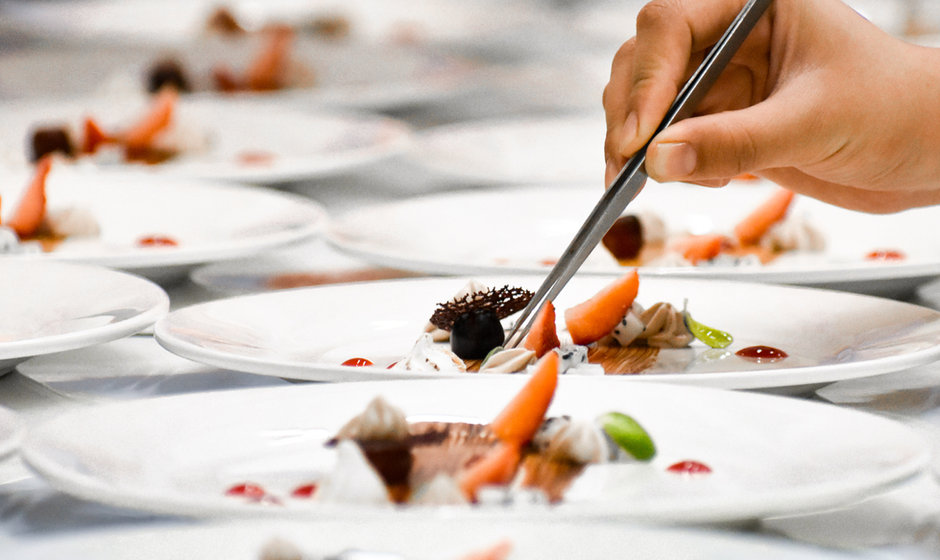 A chef decorates many plates of cake.jpg