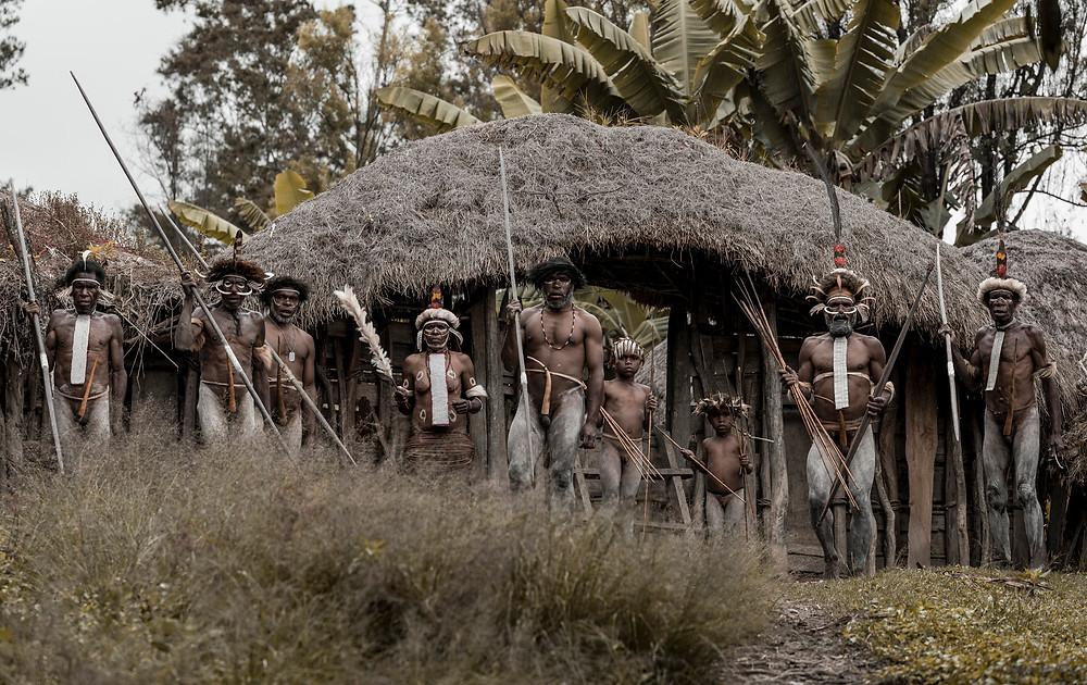 Ein Dani Stamm vor dem Eingang zu ihrem Dorf.