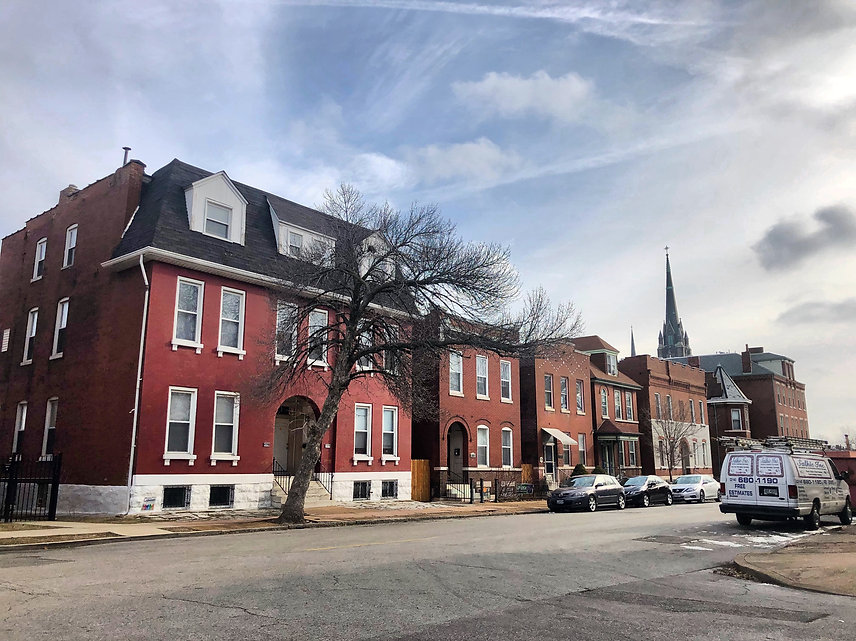 a photo of houses and buildings in St. Louis, with cars parked on the street
