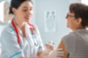 doctor-vaccinating-a-woman-BTQSPR6.jpg