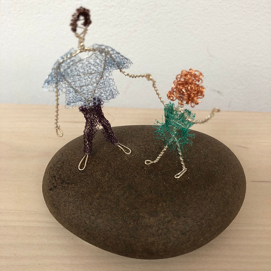 Miniature wire figures dancing on a pebble by Gwenan Bain