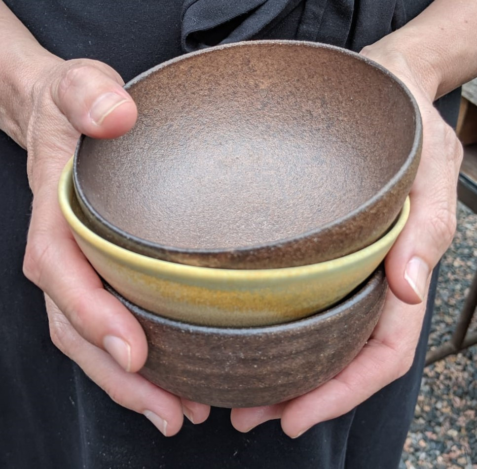Hands holding three small ceramic bowls.