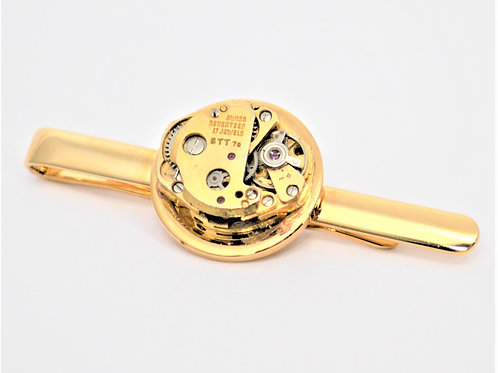 small gold watch mechanism on a gold tie slide