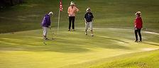 Golfers lining up putt
