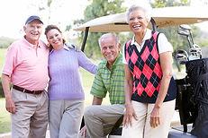 Retirees smiling sat on golf cart