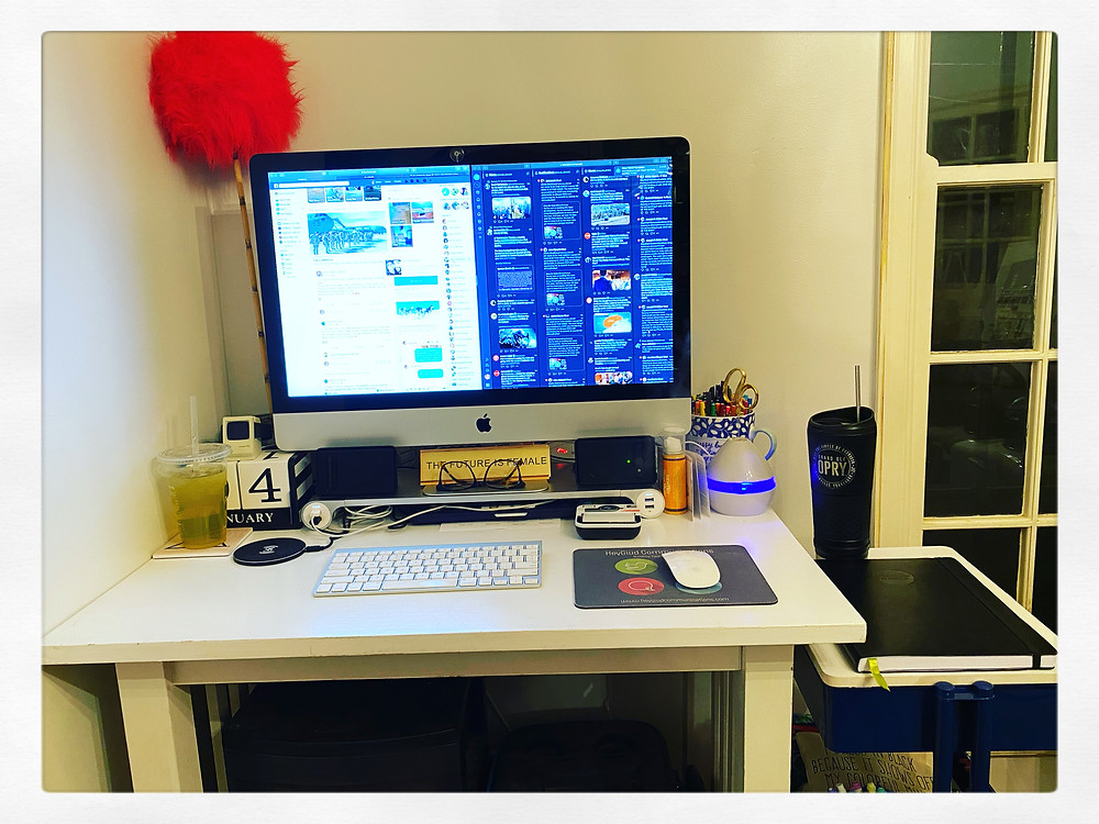 Image is of a desk with an iMac on it.