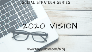 "image is of a desk with a silver laptop that has a pair of black glasses on it reading ""Social Strategy Series: 2020 Vision"""