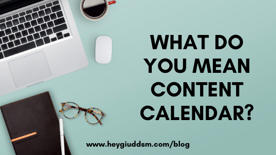 "Photo is of an aqua desk with a silver MacBook laptop, white computer mouse, cup of coffee, black notebook with white pen, and a pair of tortoise shell glasses with ""What do you mean Content Calendar?"" written in black"