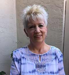 A white woman with sort hair wearing a warm smile