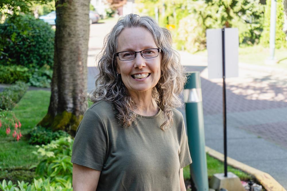 Sue, SVSS Volunteer standing outside near a garden