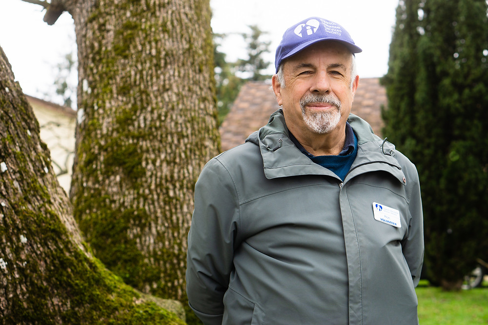 Saanich Volunteer Services Society VAC Member, Ron, standing in front of Garry Oak trees