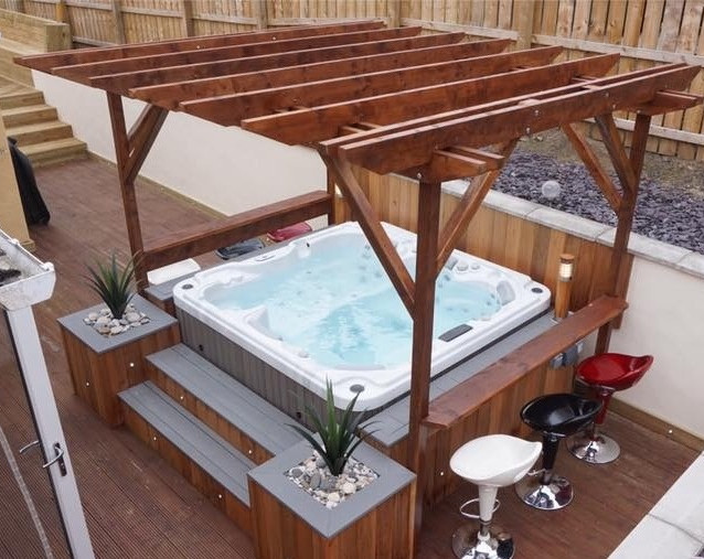 Fiji 6 seater spa, with cedar planters & steps, with bespoke pergola and side bars.