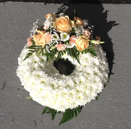 Based open wreath with a peach corsage