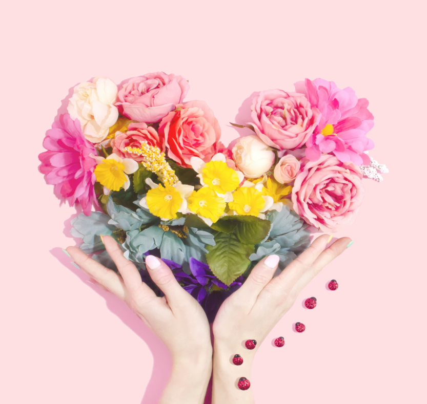 hands holding flowers forming a heart