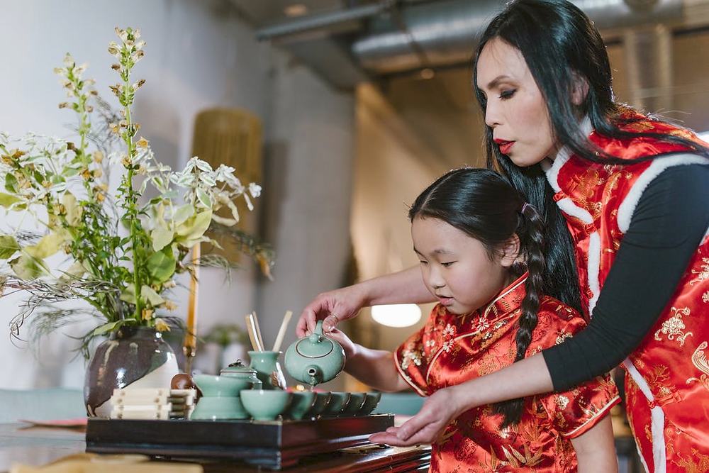 A mother is helping her daughter pour into a cup, with flowers on the table