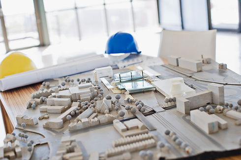 illustration-of-city-scape-urban-engineering-3d-buildings-architectural-models-on-desk-with-yellow-and-blue-safety-helmets