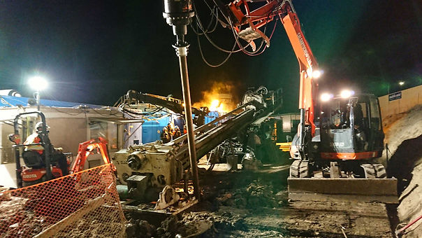 An excavator installing a screw pile at night to stabilize a drilling rig in an emergency situation.