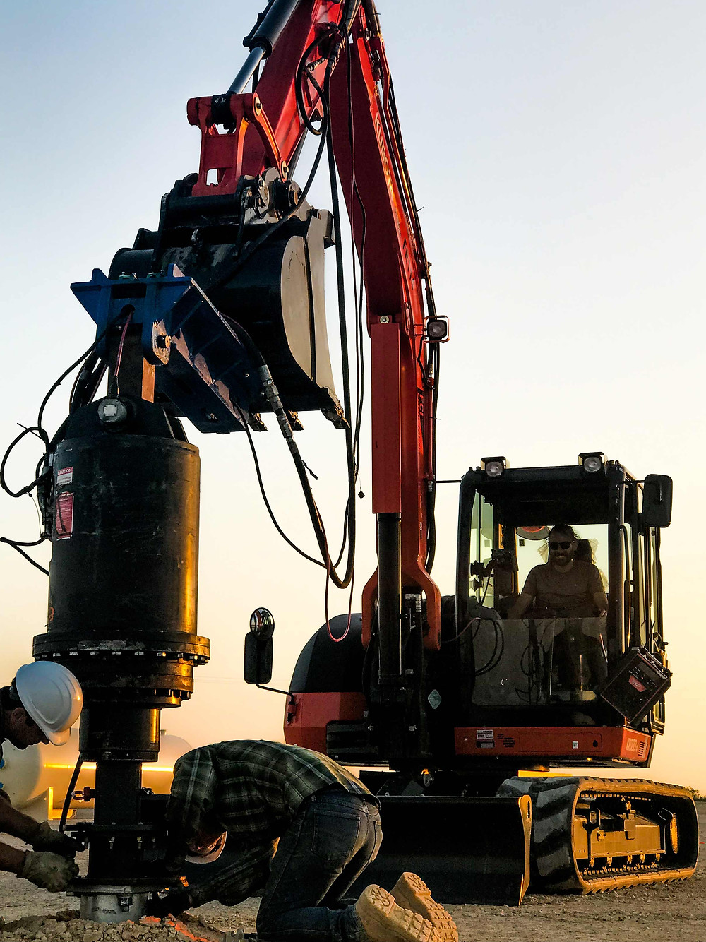 Screw piles being installed by an excavator and crew at a petroleum facility in Texas.