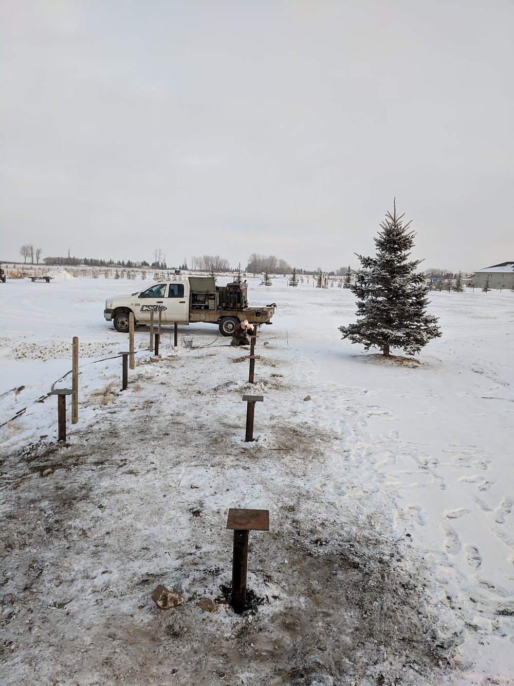 Screw piles installed in the snow at a construction site in Alberta, Canada.