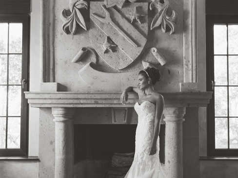 Bride in front of family crest on fireplace