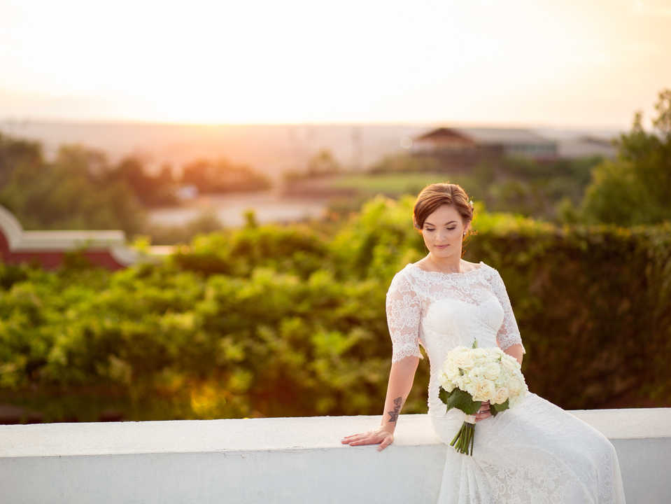 Bride on outdoor balcony at sunset