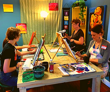 4 ladies painting on a table.png