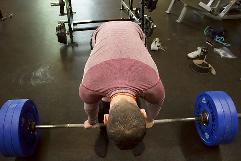 Lifter reaching down and grabbing a barbell with weights in preparation to lift it.