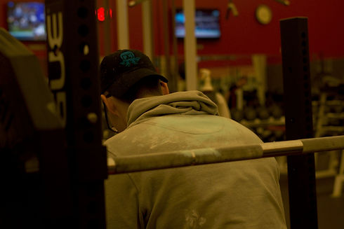 Lifter sitting on a bench press in a hoodie with blue chalk on the back and on the barbell.