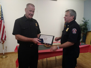 Greg recievs certificate of hire from retiring Chief Edwards