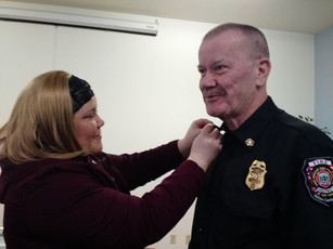 Gregs daughter pins on his insignia. A Family member pinning the insignia is a Fire service tradition
