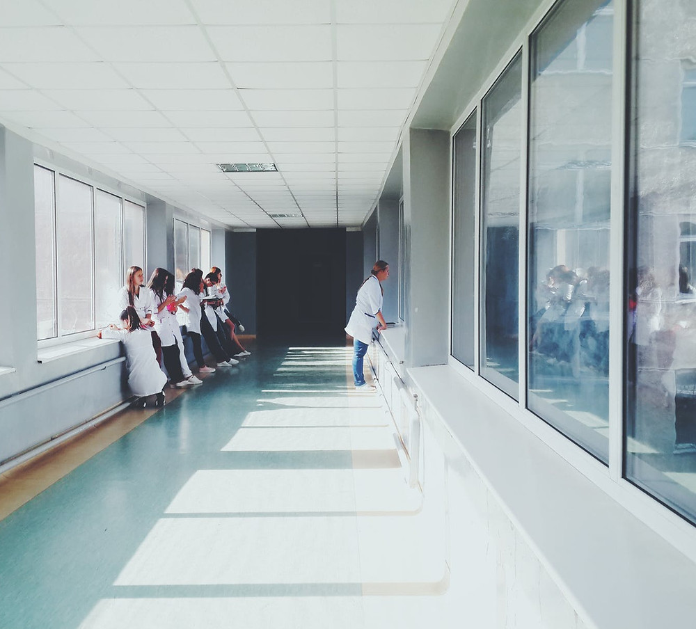 long hallway with white ceiling, walls and linoleum floor, a number of young people in white coats looking out a window