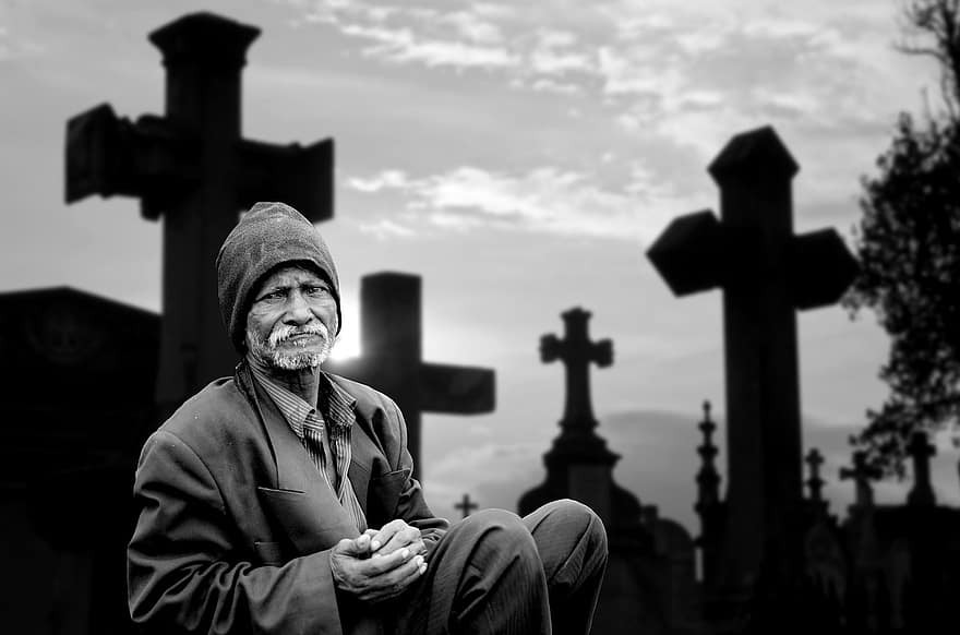 Man sitting in cemetery surrounded by crosses. Photo by Pikist.