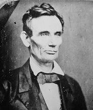 Abraham Lincoln in a suit and bow tie and flopped collar. He is unsmiling and not looking at the camera.