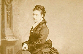 Molly Edwards - photo of a young woman in crepe early bustle dress with lace collar. Her hair is in a high bun atop her head with ornamental pins. She has a content expression.