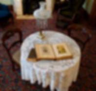Table with historic photo album and lamp on top. Two chairs at table. Two chairs in background with the bottom of a fireplace showing.