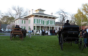 Edwards Place exterior. Two horse-drawn carriages approach the home from a large lawn. A crowd dressed in 19th century attire stand in front of the home. Trees are around the side and back of thehome, some with leaves, some without.