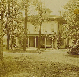 Historic image of Edwards Place in sepia tone with many thin trees in front.