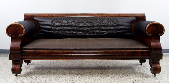 A long sofa upholstered in black horsehair and embossed with an elaborate design on the back.