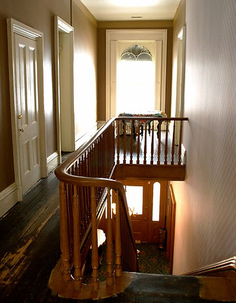 An upstairs hallway with unfinished floors and a wooden banister.